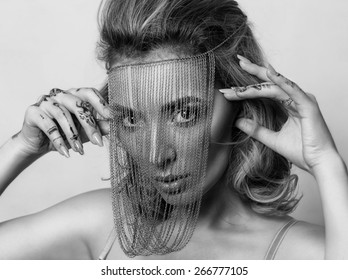 Close-up portrait of young beautiful woman with smoky make-up and chains over her face