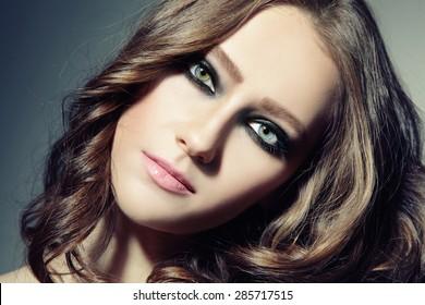 Close-up portrait of young beautiful woman with stylish smokey eyes