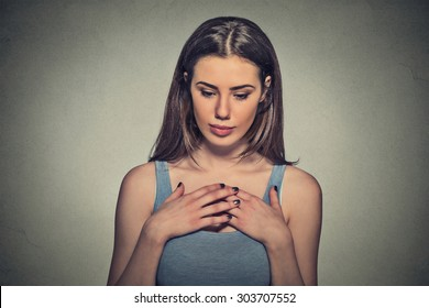 Closeup portrait young beautiful woman, shy, playing nervously with hands looking down, feeling guilty, sorry for actions, faults did wrong, isolated on gray background. Expression, emotion, reaction