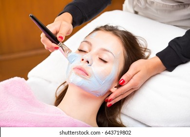 Close-up portrait of young beautiful woman during spa, while hands of female cosmetologist applying blue mask to her face with wide brush