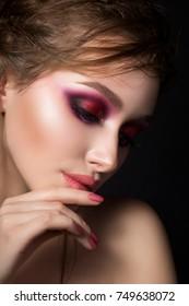 Closeup portrait of young beautiful woman with bright pink smokey eyes. Girl touching her lips. Fashion makeup. Studio shot. Modern summer make up