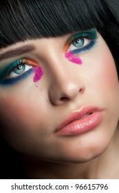 Close-up portrait of young beautiful woman with colorful stylish make-up looking up
