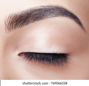 Close-up portrait of young beautiful woman's closed, female eye zone make up