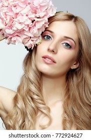 Closeup portrait of young beauty female face with blond hair and hydrangea bouquet flowers near face