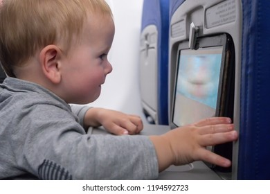 Closeup portrait of young blond baby watching tablet sitting with mother while travelling air plane