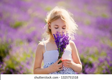 Close-up portrait of young blonde girl in the colour dress in the field of lavander with a small bouqet in her hands.