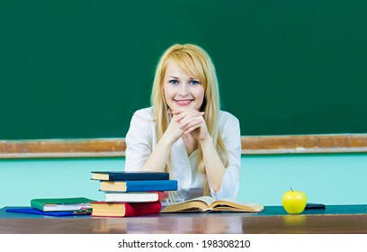 Closeup portrait young blonde woman, smiling student, teacher sitting at desk studying in class room isolated background chalkboard. Facial expression, education, college university life style concept
