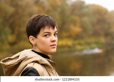Close-up portrait of a young brunette girl with ultra short pixie hairstyle in autumn yellow park. In a jacket with a hood.