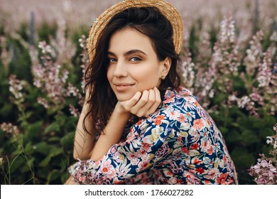 Close-up portrait of a young brunette woman wearing a straw hat and a floral dress in a field with sage flowers in bloom.