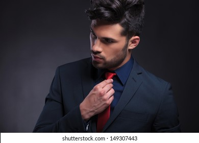 closeup portrait of a young business man adjusting his tie and looking away from the camera. on a black background