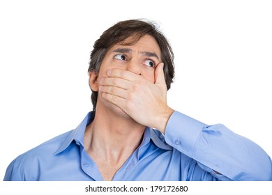 Closeup portrait of young business man, student worker, scared employee covering his mouth. Speak no evil concept isolated on white background. Human emotion face expression feeling sign body language