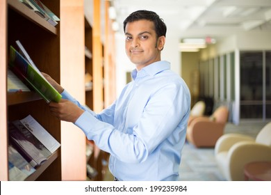 Closeup portrait, young business man in blue shirt reading, perusing books, magazines, and periodicals at library