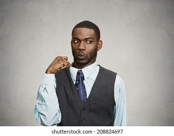 Closeup portrait, young business Man opening shirt to vent, it's hot, Unpleasant, Awkward Situation, Embarrassment. Isolated black, grey background. Negative Emotions, Facial Expression, Feelings
