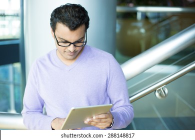 Closeup portrait, young captivated, absorbed, engrossed man in purple sweater and black eye glasses perusing, pondering emails on silver gray tablet touch-pad, isolated indoors background