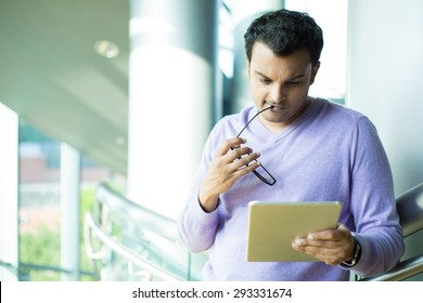 Closeup portrait, young captivated, absorbed, engrossed man in purple sweater biting black eye glasses, perusing, pondering emails on silver gray tablet touch-pad, isolated indoors office background