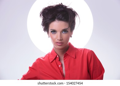 closeup portrait of a young casual woman with shining aura around head, looking into the camera with a serious expression. on gray background