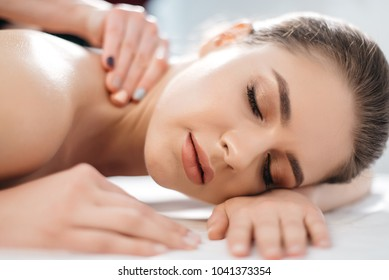Close-up portrait of the young caucasian attractive woman with natural make-up is resting with closed eyes during the massage in spa salon.