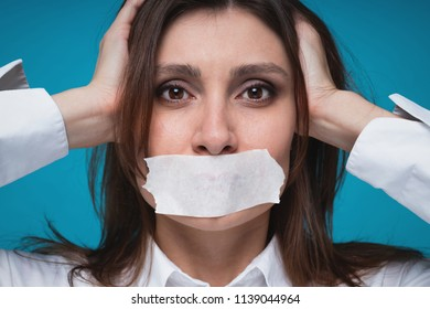 Closeup portrait of young caucasian brown-haired girl in fright clings to her head with her hands, the mouth is sealed with a white plaster. Text space. #metoo movement concept.