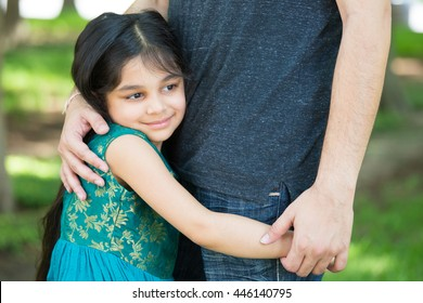 Closeup portrait, young child hugging her father tenderly, isolated outdoors outside green grass background. Daddy's little girl