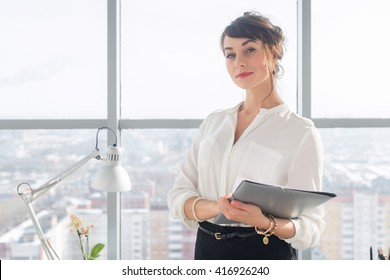 Close-up portrait of a young confident female office manager at her workplace, ready for doing business task.