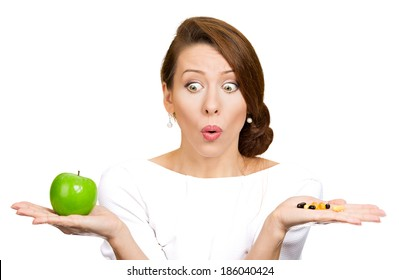 Closeup portrait young confused, puzzled woman holding green fresh apple in one hand, pill, vitamins in another, trying to decide which choice is the best one. Face expressions, emotions, health care
