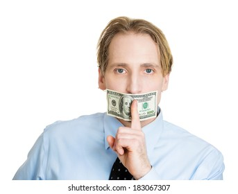 Closeup portrait young corrupt man in blue shirt with hundred dollar bill taped to mouth, showing shhh sign isolated white background. Bribery concept in politics, business, diplomacy. Life perception