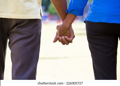 Closeup portrait of a young couple with chemistry, holding hands, happy moments, commitment, love and romance concept, positive human emotions on isolated outdoors outside park background.