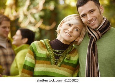 Closeup portrait of young couple embracing in autumn park.?