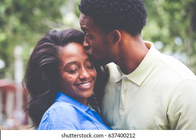 Closeup portrait of a young couple, guy in yellow shirt kissing woman with blue shirt, happy moments, positive human emotions on isolated outdoors outside background.