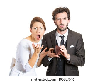 Closeup portrait young couple woman, man showing holding empty wallet, no money being broke, over budget, poor, looking surprised, isolated white background. Negative facial expression emotion feeling