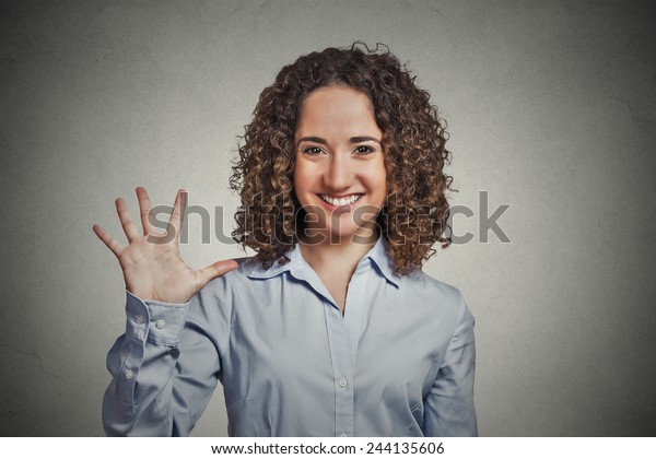 Closeup portrait, young, curly, brown hair woman, making five times sign gesture with hand fingers, isolated grey wall background. Positive human emotion facial expression feelings, attitude, symbol.