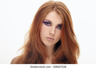 Closeup portrait of young cute redhead lady with violet smokey eyes makeup isolated
