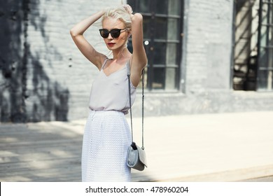 Close-up portrait of young elegant blonde woman in white dress, sunglasses and red lips touching her hair in bun. Fashion street shot