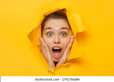 Close-up portrait of young excited woman shocked and amazed by commercial offer, looking through hole in torn paper, isolated on yellow background