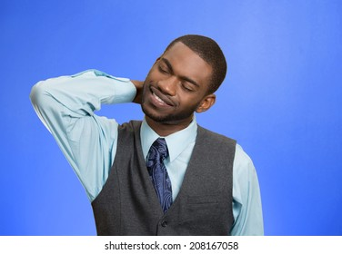 Closeup portrait, young executive man with spinal neck pain in thoracic vertebrae after long hours of work, studying, isolated blue background. Lack of ergonomic support. Face expression, feelings