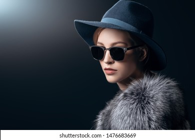 A close-up portrait of a young fashionable woman in a fur coat and sunglasses. Beauty, optics, fashion.