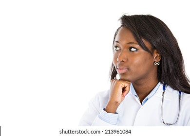 Closeup portrait, young female doctor, health care professional, daydreaming, thinking, looking up at copy space isolated white background. Patient visit health care reform. Human emotion, expression
