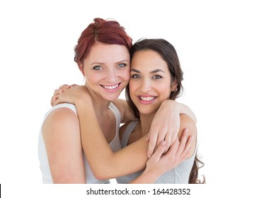 Close-up portrait of a young female embracing her friend over white background