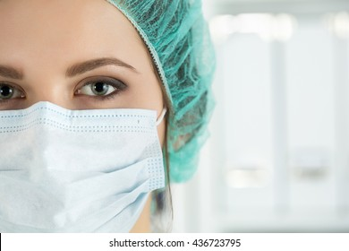 Close-up portrait of young female surgeon doctor or intern wearing protective mask and hat. Healthcare, medical education, emergency medical service, surgery or veterinary concept