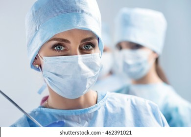 Close-up portrait of young female surgeon doctor at operation theater. Group of surgeons at work. Healthcare, medical education, emergency medical service and surgery concept