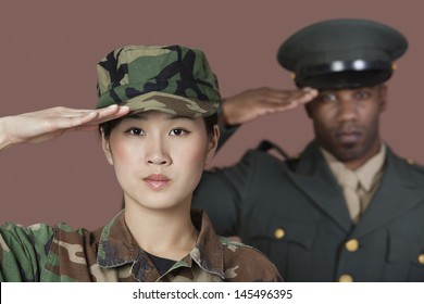 Close-up portrait of young female US Marine Corps soldier with male officer saluting over brown background