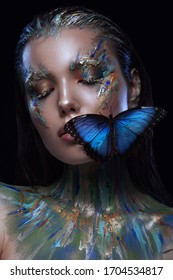 Close-up portrait of a young girl with the effect of wet skin. Creative makeup, lively blue morph butterfly on the model's face.