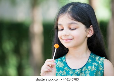 Closeup portrait, young girl enjoying orange lollipop on a sunny day, isolated green trees background
