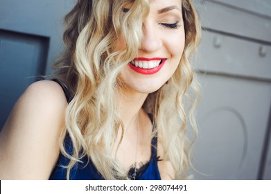 close-up portrait of a young girl hipster beautiful blonde  with red lips laughing and posing against the backdrop of the city