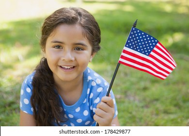 Close-up portrait of a young girl holding the American flag at the park