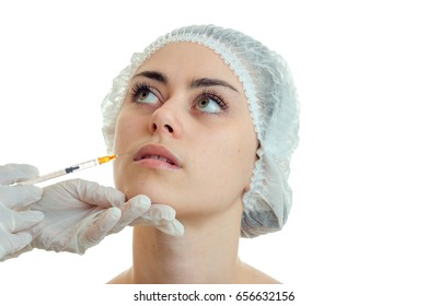 close-up portrait of a young girl in the medical CAP which has raised his eyes up and the doctor makes a prick on her face