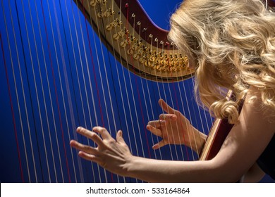 Closeup portrait of young girl playing the harp during concert at musical theater