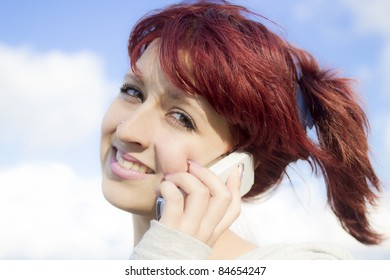Close-up portrait of young girl speaking by the telephone