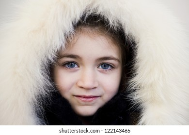 Close-up portrait of young girl wearing fur hood and smiling