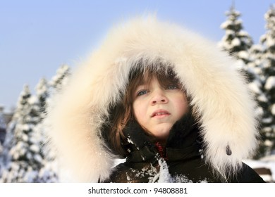 Close-up portrait of young girl wearing fur lined coat hood